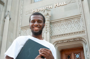 student with folder outside Hepburn Hall