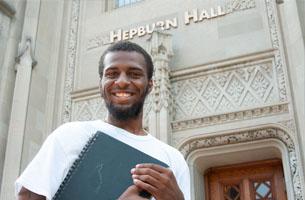 student with folder outside Hepburn Hall
