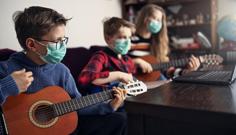 Brother and sister playing guitars together - stock photo GettyImages-1214130327