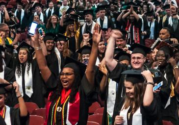 crowd of students at graduation cheering