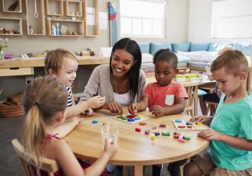 female teacher teaching young children at round table