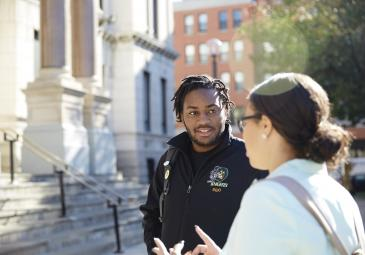 male and female student talking in front of city hall downtown jersey city
