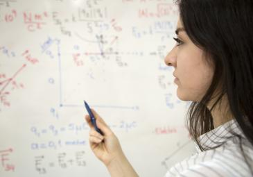 female math student working out equations on whiteboard