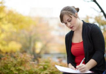 tuition fees scholarships female student writing outside