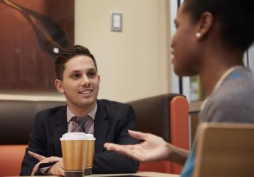 two business students conversing in dunkin donuts