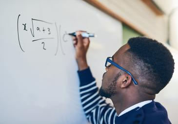 male math student working out equations on whiteboard