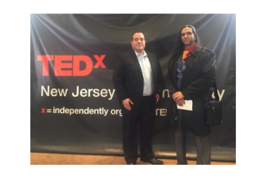 Two gentlemen in front of TEDx sign