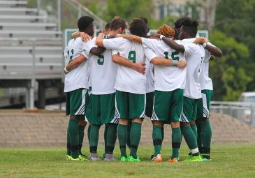 NJCU men's soccer team in a huddle