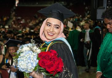 Student at graduation with flowers