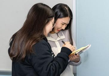 Two students smiling and reviewing a notebook together