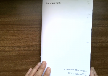 Hands opening a handmade book titled Are You Upset
