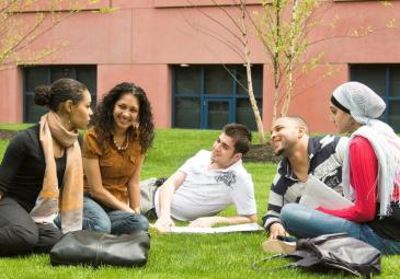 A diverse group of 3 female and 2 male students sitting and talking on a lawn on campus.