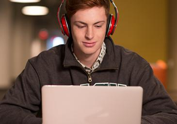 student at a laptop wearing headphones