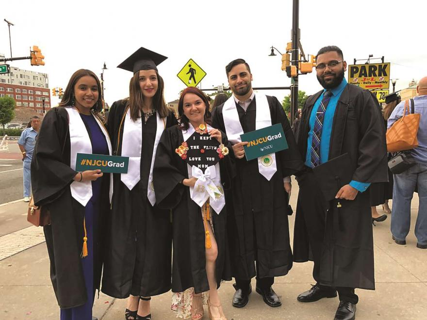 5 graduates holding #NJCUGrad signs and decorated cap.