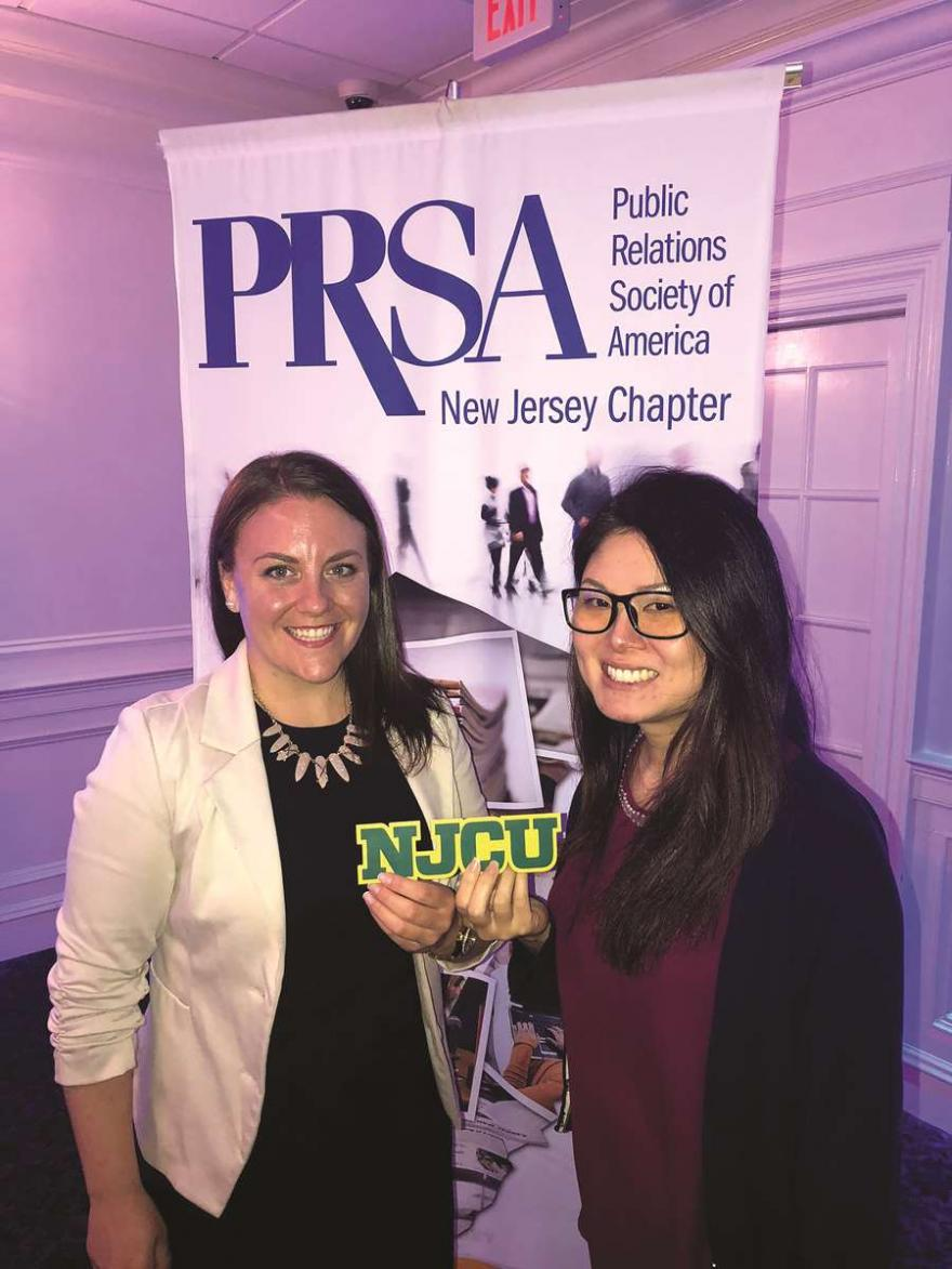 Nicole and Thi hold NJCU in front of PRSA New Jersey Chapter banner.