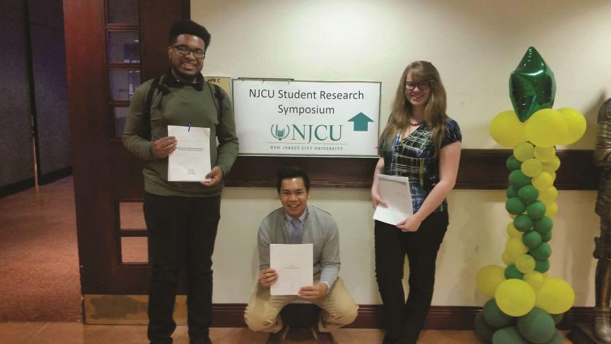NJCU students holding research papers outside Student Research Symposium.