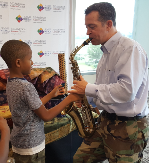 Man playing the saxophone with child