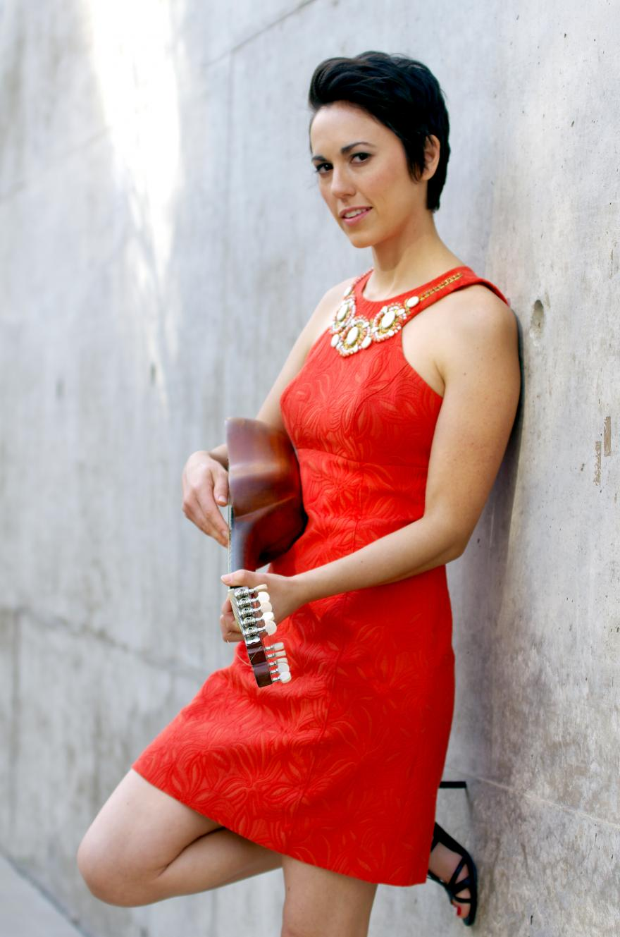 Gina Chavez in red dress holding string instrument