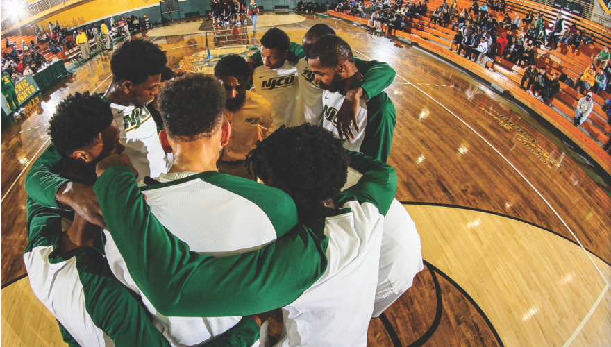 NJCU men's basketball team huddled on the court.