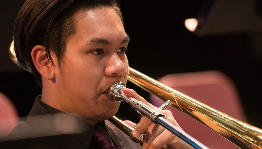 male student playing slide trombone