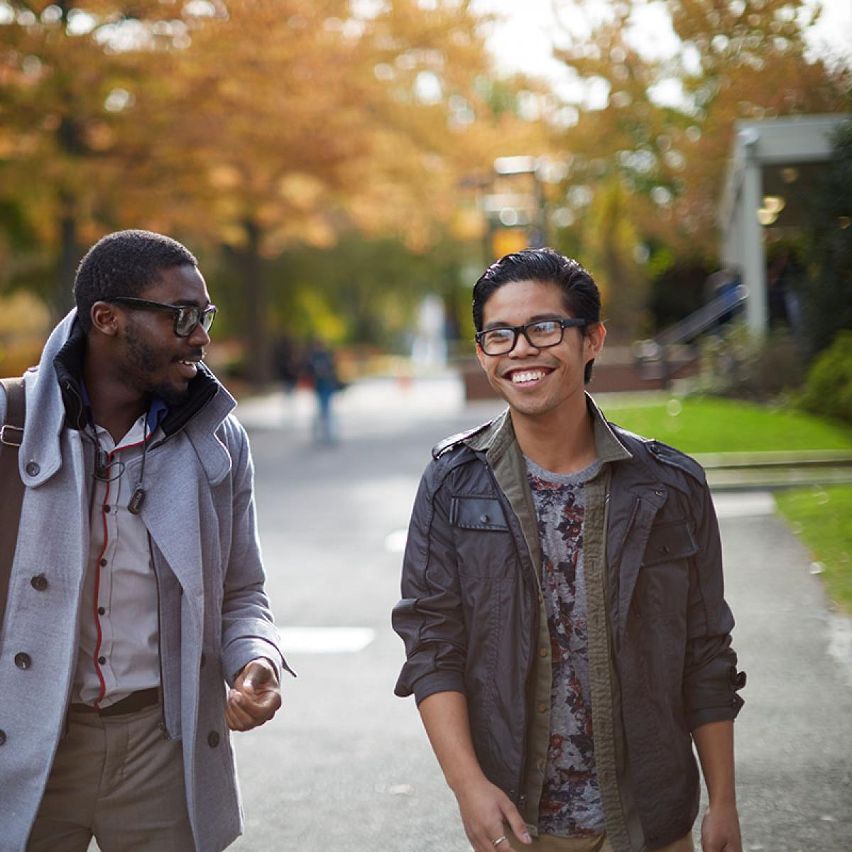 Two male students walking and talking through campus Fall background