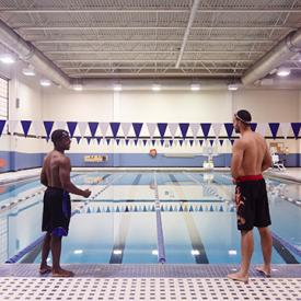 two male students standing at edge of pool fitness center