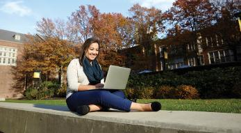 female student sitting on campus with a laptop