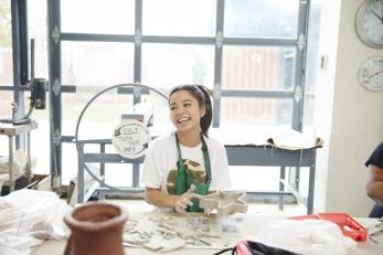 female student smiling in ceramics room