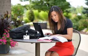 Student sitting with laptop and textbook