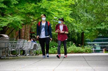 two students wearing masks walking on campus