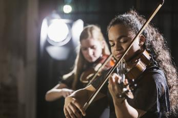 Two young women playing string instruments
